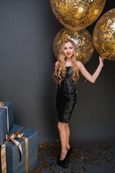 Полнометражный портрет удивительной молодой женщины с длинными светлыми волосами, держащей сверкающие воздушные шары. студийное фото довольно европейской дамы в черном платье, стоящего возле настоящих коробок.