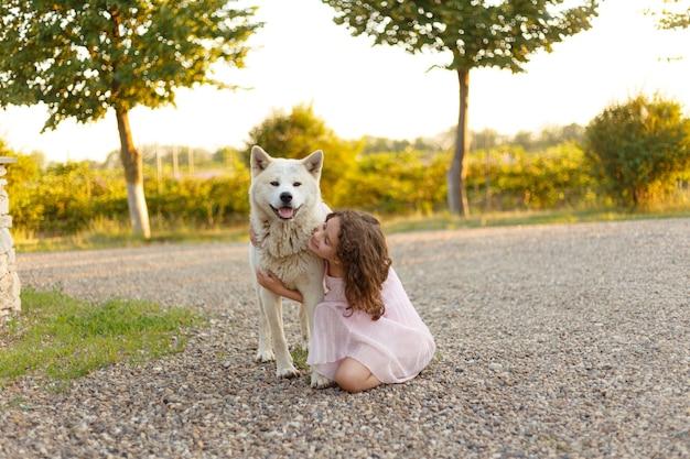 Портрет очаровательной маленькой девочки в полный рост обнимает свою большую собаку, проводящую время вместе на улице летом. место для текста.