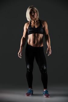 魅力的な筋肉のスポーツウーマンの完全な長さの肖像画