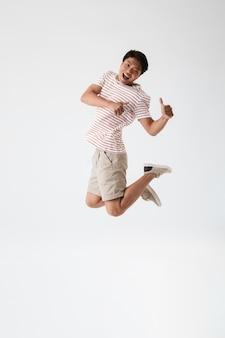 Портрет возбужденного молодого азиатского мужчины в полный рост