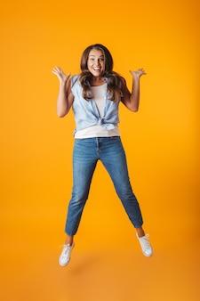 Портрет возбужденной молодой случайной женщины в полный рост, прыгающей, празднуя успех