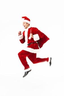 サンタクロースの衣装に身を包んだ興奮した若い男の完全な長さの肖像画は、白いスペースに孤立してジャンプします。 Premium写真