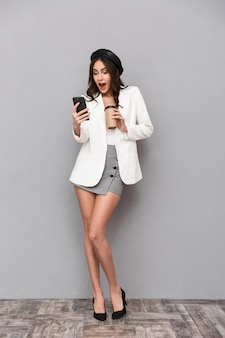 Полный портрет возбужденной молодой женщины, одетой в мини-юбку и пиджак на сером фоне, держащей чашку кофе и использующей мобильный телефон