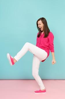장미 셔츠 블라우스에 화가 재미 젊은 예쁜 여자의 전체 길이 초상화, 흰 바지는 밝은 핑크 블루 파스텔 벽에 고립 된 포즈.