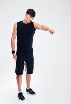 Полный портрет разъяренного спортсмена, показывающего пальцем на чем-то изолированном