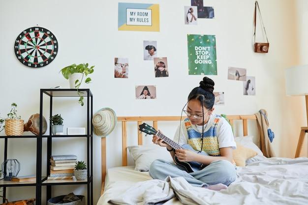 Портрет в полный рост азиатской девочки-подростка, играющей на укулеле, сидя на кровати в уютной комнате, копией пространства