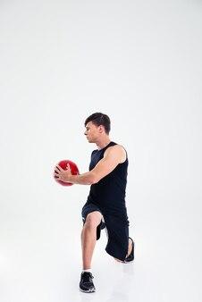 分離されたフィットネス ボールで運動する男の完全な長さの肖像画