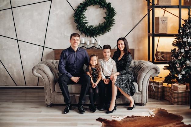 モダンなソファに座ってカメラに微笑んでいる娘と息子とエレガントな服を着た魅力的な大人の親の完全な長さの肖像画。後ろの壁にクリスマスリース。