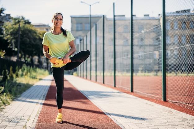 Полнометражный портрет привлекательной брюнетки пригонки протягивая ноги после тренировки на свежем воздухе.