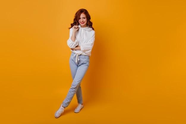 생강 머리를 가진 매력적인 여자의 전신 초상화. 행복한 아가씨의 실내 촬영은 흰색 스웨터와 청바지를 착용합니다.