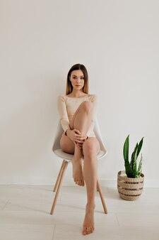 Портрет в полный рост привлекательной красивой европейской женщины в бежевом теле с естественным макияжем и светлыми волосами, позирующей перед камерой над белой стеной