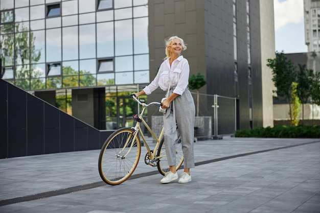 현대적인 비즈니스 센터 앞에 자전거가 서 있는 매력적인 웃는 여성의 전체 길이 초상화