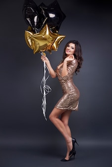 Портрет привлекательной женщины в полный рост с воздушным шаром