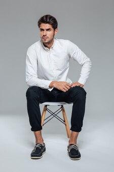 Портрет в полный рост привлекательного молодого человека в белой рубашке, сидящего на стуле над серой стеной
