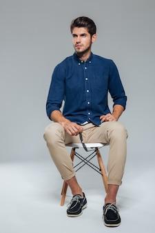 Портрет привлекательного молодого человека в полный рост, сидящего и держащего солнцезащитные очки над серой стеной