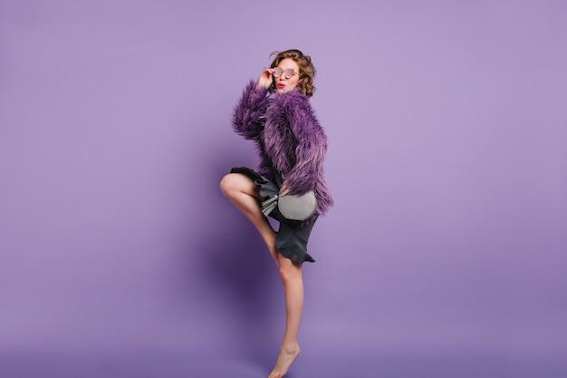 Портрет в полный рост босоногой девушки, стоящей на носках во время фотосессии в зимней куртке