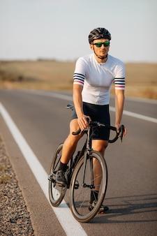 자전거와 함께 포즈를 취하는 흰색 티셔츠와 검은 색 반바지에 수염 난 남자의 전체 길이 초상화