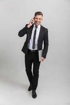 孤立して立っている間ラップトップを保持し、スマートフォンで話しているオフィススーツの美しい大人のビジネスマンの完全な長さの肖像画