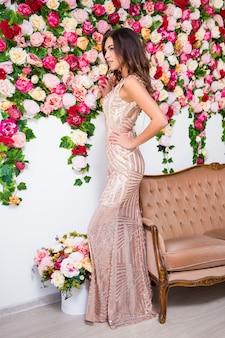 화려한 꽃 배경 위에 빈티지 소파가 있는 드레스를 입은 아름다운 소녀의 전체 길이 초상화