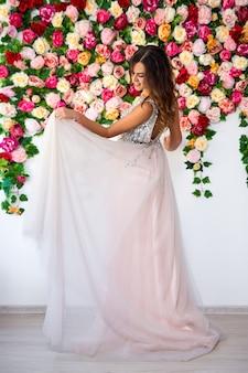 화려한 꽃 배경 위에 긴 드레스를 입은 아름다운 소녀의 전체 길이 초상화