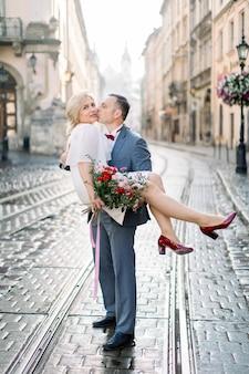 고 대 오래 된 도시에서 아름 다운 성숙한 부부의 전체 길이 초상화. 양복을 입은 잘생긴 남자는 매력적인 금발 여성을 손에 들고 그녀의 뺨에 키스합니다. 결혼 기념일 축하