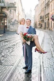 고 대 오래 된 도시에서 아름 다운 성숙한 부부의 전체 길이 초상화. 양복을 입은 잘생긴 남자는 매력적인 금발 여자를 손에 들고 있다. 결혼 기념일 축하