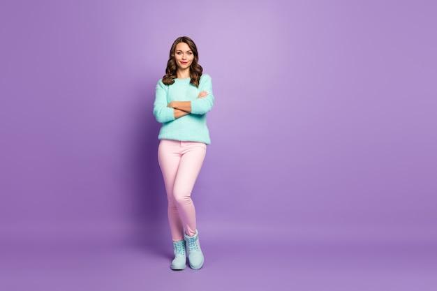 美しいきれいな女性の巻き毛の髪型の良い気分の腕を交差させた自信のある人の全身像は、パステルカラーのふわふわのセーターピンクのパンツの靴を履いています。