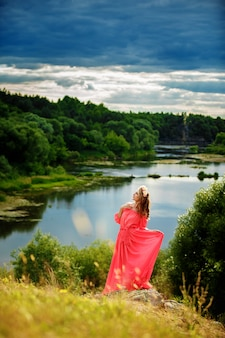Полная длина портрет красивой чувственной молодой блондинкой в длинном розовом платье и венок возле озера на открытом воздухе в естественных