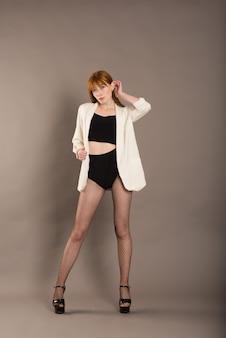 格子縞のジャケット、白い水玉のタイツ、ブーツを着た美しい女性の全身像