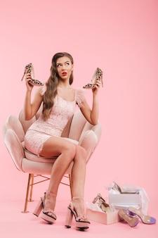 Полный портрет красивой женщины в платье, делающей покупки и выбирающей обувь, сидя в кресле, изолированной над розовой стеной