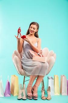 Полный портрет красивой женщины в платье, делающей покупки и держащей коробку с красной обувью, сидя на кресле, изолированной над синей стеной