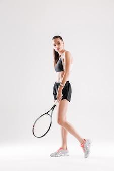 スポーツ衣料品の美しい若い女性の完全な長さの肖像画