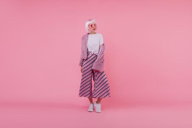 至福の女性モデルのフルレングスの肖像画は、流行のパンツと短いふわふわのジャケットを着ています。白い靴でポーズをとるピンクの髪の深刻な女性