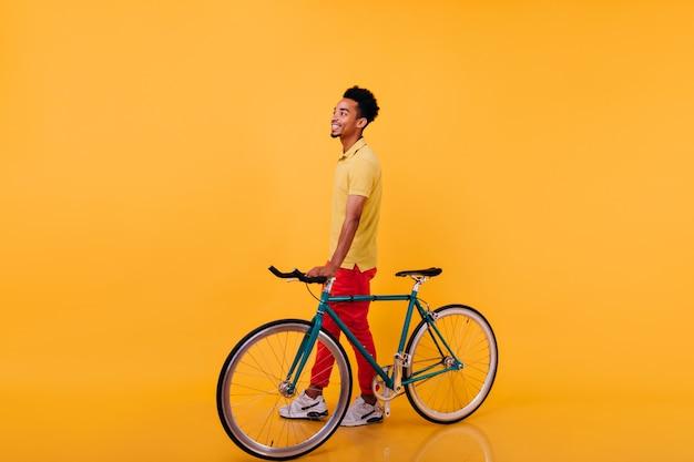 自転車でポーズをとる陽気なアフリカ人の全身像。立っているスポーツシューズのトレンディな黒人男性の写真。
