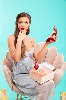 Портрет в полный рост задумчивой женщины в платье, сидящей в кресле и смотрящей в сторону с красной обувью в руке во время покупок, изолированные на синей стене