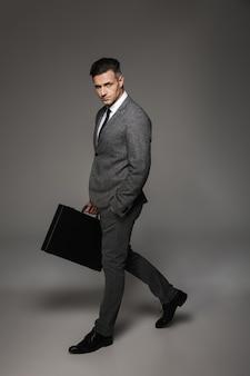 歩くと灰色の壁に分離されたブリーフケースを手で運ぶ正式な衣装に身を包んだブルネットのビジネスの男性の完全な長さの肖像画
