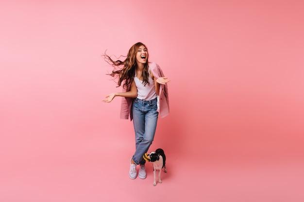 강아지와 함께 포즈를 취하는 청바지에 갈색 머리 아가씨의 전신 초상화. 프랑스 불독 옆에 서있는 아름 다운 여성 모델의 실내 초상화.