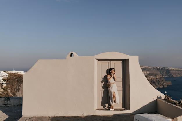 Полный портрет брюнетки в бежевом платье позирует возле здания с видом на море