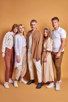 Портрет спокойных друзей студентов в модной одежде в полный рост, позирующих вместе