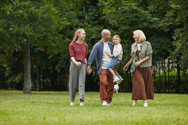 Портрет беззаботной семьи в полный рост с двумя дочерьми, стоящими на зеленой траве на открытом воздухе, наслаждаясь прогулкой в парке вместе