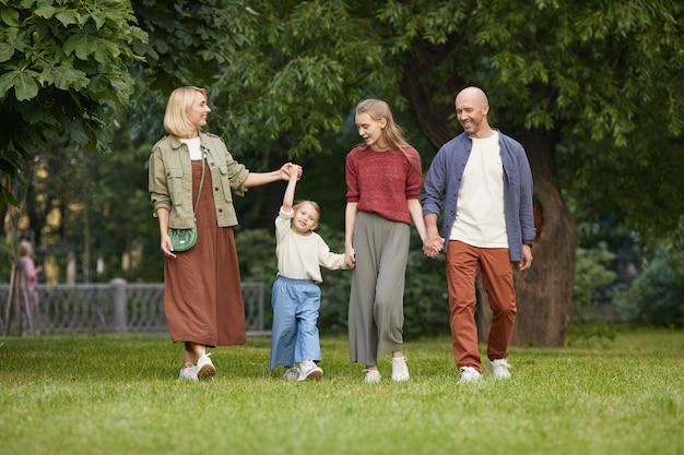 Портрет беззаботной семьи в полный рост с двумя детьми, держась за руки во время прогулки по зеленой траве на открытом воздухе
