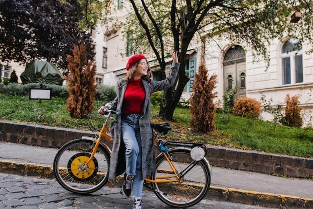 Портрет беззаботной молодой женщины в винтажных джинсовых штанах в полный рост, позирующей на фоне красивой природы