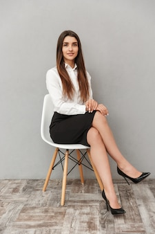 회색 벽 위에 절연 의자에 앉아있는 동안 웃고 비즈니스 착용에 긴 갈색 머리를 가진 백인 여자의 전체 길이 초상화