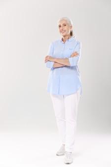 교차 손으로 서 파란색 셔츠와 흰색 바지에 매력적인 할머니의 전신 초상화