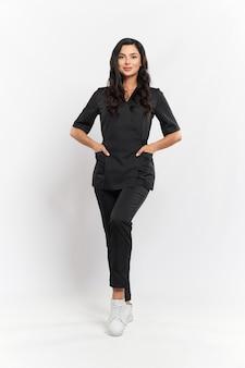 Портрет очаровательного профессионального косметолога в черной медицинской форме в полный рост, стоящего на белом