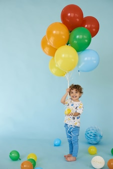 青い背景、誕生日パーティーのコンセプトに対してポーズをとって風船を保持している陽気な少年の全身像