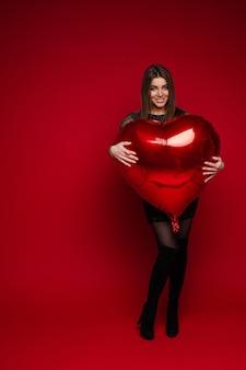 赤い背景に赤いハート型の風船を抱きしめるドレスとブーツの陽気なブルネットの少女の全身像。聖バレンタインのコンセプト。