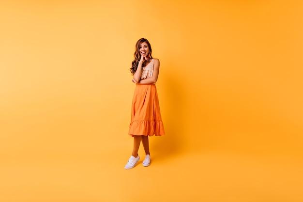 陽気な生姜の女性の全身像。オレンジ色の服を着たロマンチックな白人の女の子
