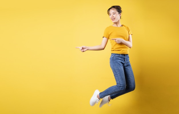 黄色の背景で隔離の元気な女の子のジャンプの完全な長さの肖像画
