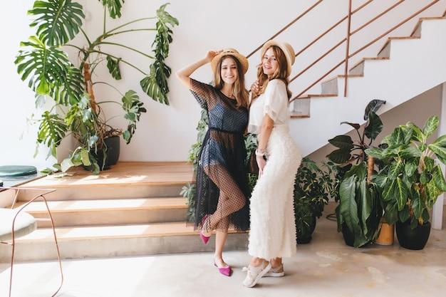 Портрет в полный рост веселых девушек, танцующих вместе на лестнице и смеющихся